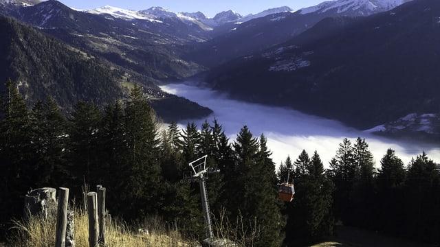 Blick von Brambrüesch auf ein Nebelmeer im unteren Schanfigg. Dahinter die grünen Hänge Richtung Glaspass.