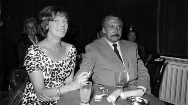 Ein Mann mit Schnauz neben einer rauchenden Frau.