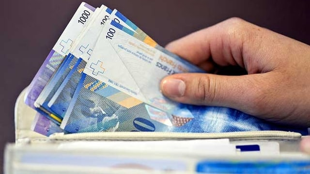 Eine Hand hält mehrere Banknoten, die aus einem Portemonnaie hervorragen.