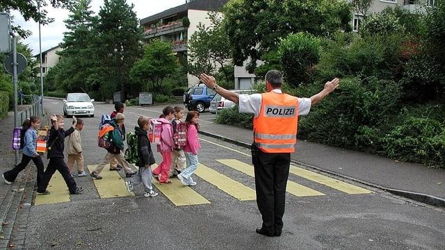 Ein Polizist vor einem Zebrastreifen mit Schulkindern