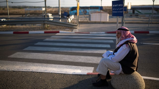 Ein Mann mit rotem Arafat-Kopftuch sitzt auf einem Stein an einer Strasse mit Fussgängerstreifen.
