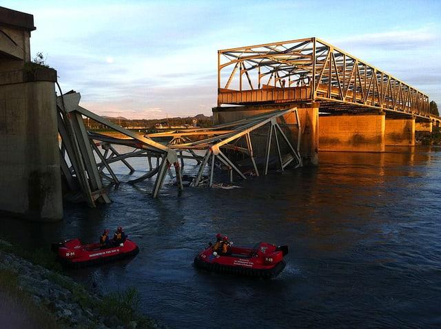 Blick auf die eingestürzte Brücke. Im Wasser fahren Rettungsboote.