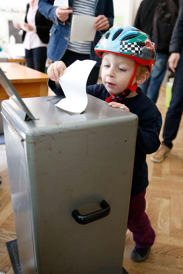 Kind mit Velohelm steht vor einer Wahlurne und lässt einen Wahlzettel in den Schlitz fallen