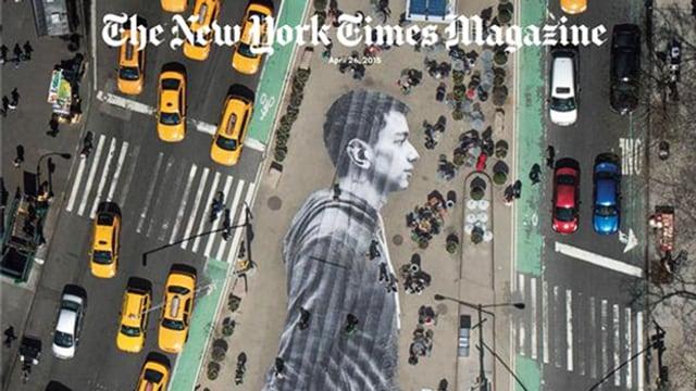 Auf der Strasse einer Grossstadt klebt ein momumentales schwarz-weisses Bild eines jungen Mannes.