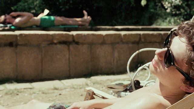 Ein Mann liegt in Badehosen in einem Liegestuhl, im Hintergrund ein anderer am Rand eines Pools.