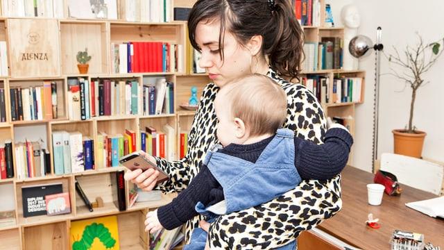 Eine Frau hält ihr Baby auf dem Arm und ein Handy