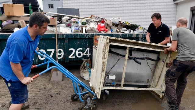 Männer tragen verschmutzte Haushaltgeräte aus dem Haus und entsorgen sie in einer Mulde
