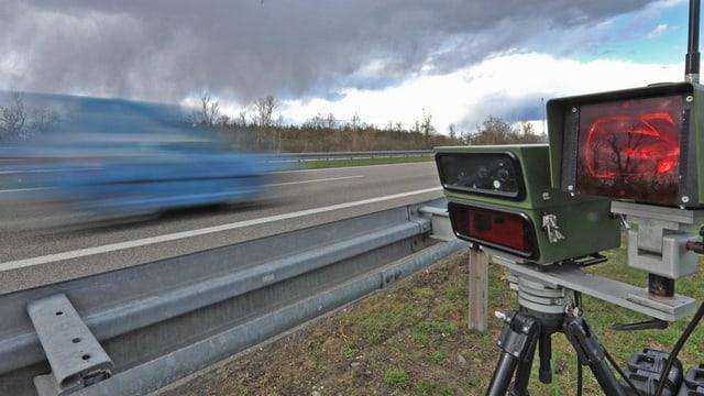 Blitzlichtanlage einer Radarkontrolle mit blauem Auto, das vorbei rast.
