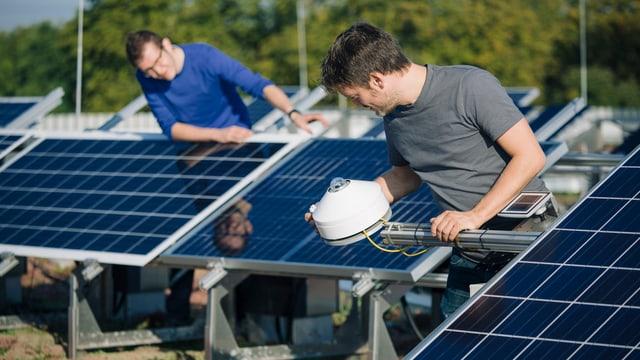 Zwei Männer arbeiten an blauen Solaranlagen.
