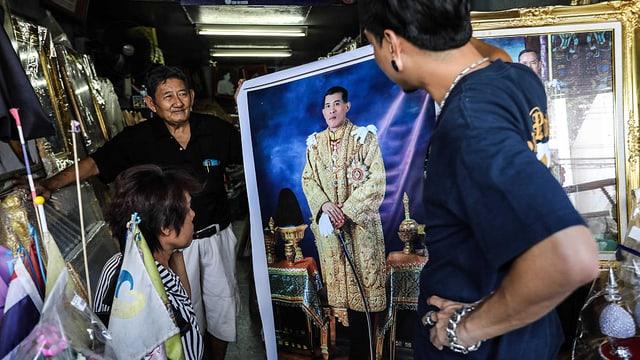 Drei Personen sehen sich in einem Geschäft ein grosses Porträt-Bild Vajiralongkorns an.