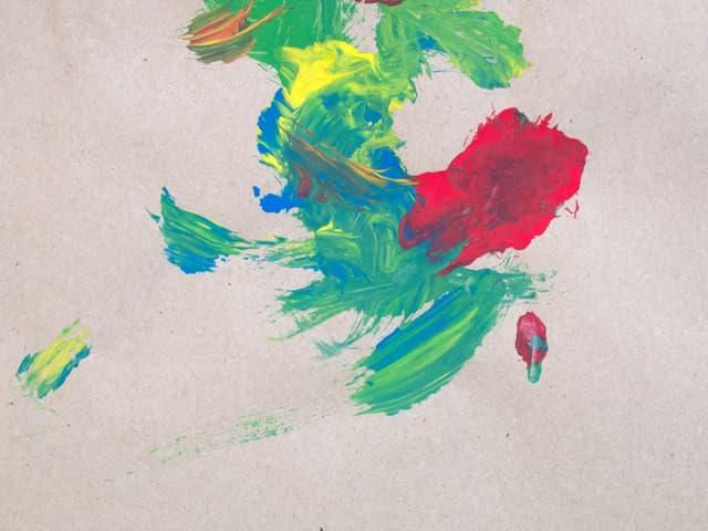Auf einem Blatt Papier sind Farbkleckse in grün, blau, rot und gelb zu sehen.