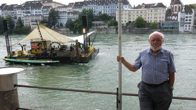 Peter Feiner steht vor dem Rhein. Im Hintergrund ist das Floss der konzertreihe «im Fluss» zu sehen.