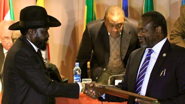 Kiir mit Hut und Machar schütteln sich die Hand.