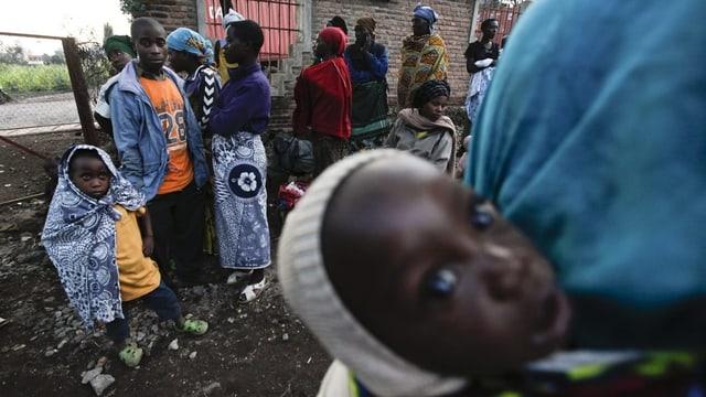 Schwarze Menschen auf der Flucht, im Vorderund ein Baby, das mit grossen Augen in die Kamera blickt.