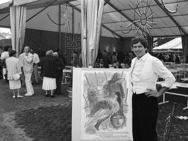 Ein Mann posiert mit einem Plakat