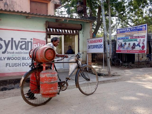 Ein Mann schiebt ein Fahrrad mit Gaskartuschen.