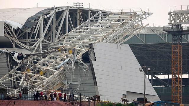 Ein umgekipptes Gerüst hat eine Mauer und das Dach eines Stadions beschädigt.