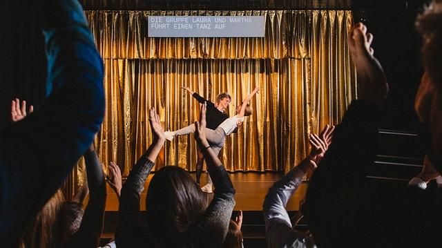 Zwei Menschen auf einer Bühne vor goldenem Aushang, Publikum