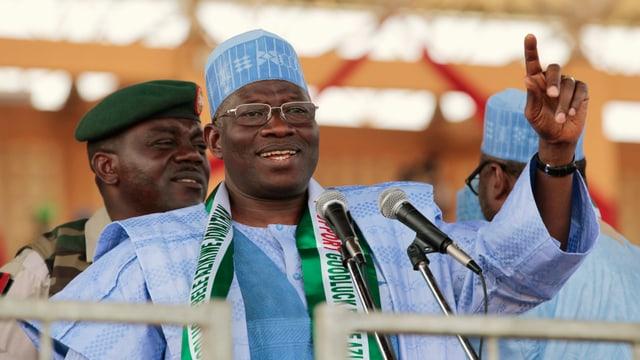 Goodluck Jonathan en vestgì cler blau discura en dus microfons