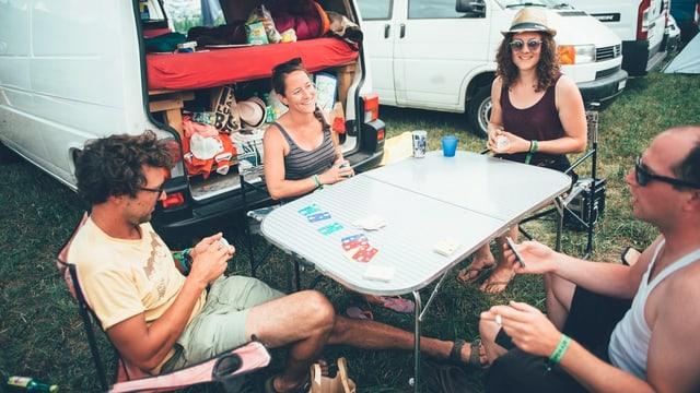 Menschen sitzen am Openair um einen Tisch und spielen Karte