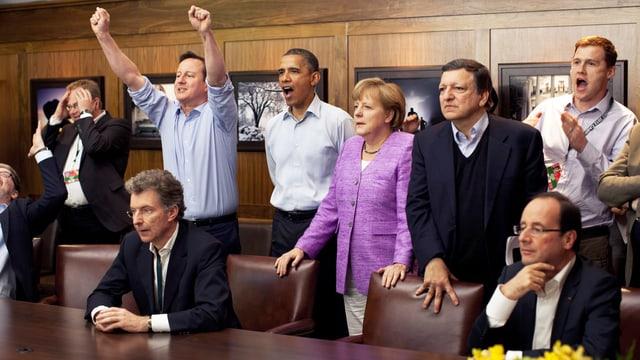 Cameron, Obama, Merkel und weitere Staatspräsidenten schauen sich ein Fussballspiel an.