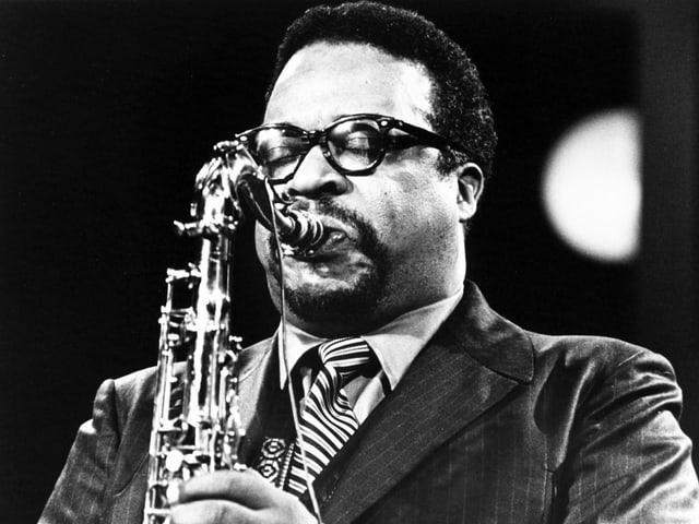 Gene Ammons trägt eine Brille. Er spielt Saxofon.