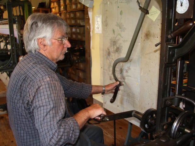Der Handsticker sitzt vor einer Vorlage und bedient mit seinen Händen Instrumente der Stickmaschine.