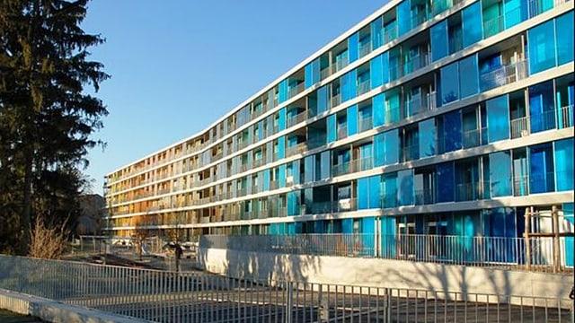 langes Gebäude mit vielen Fenstern und blauer Glasfassade