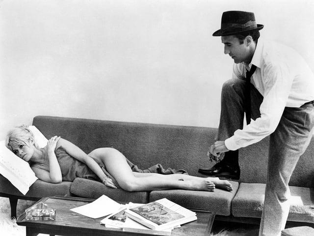 Ein Mann beim Anziehen, er steht neben dem Bett, darin liegt eine Frau.