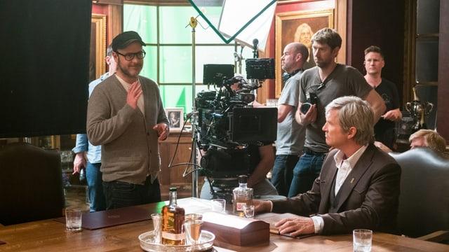 Filmset: Ein Mann sitzt am Tisch, ein Mann steht links von ihm, hat die Hand erhoben und scheint etwas zu erklären. Um die beiden herum stehen die Kameras und ein Film-Team.