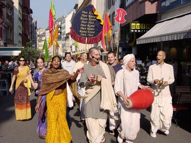 Eine Gruppe indisch gekleiderter junger Leute in einer Einkaufsstrasse. Sie singen und machen Musik.