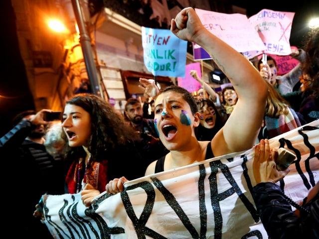 Frauen recken die Fäuste und tragen ein Transparent in den Strassen Istanbuls.