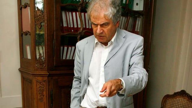 Frido Mann, in weissem Hemd und grauem Sakko zeigt auf etwas. Sein Gesichtsausdruck: kritisch.