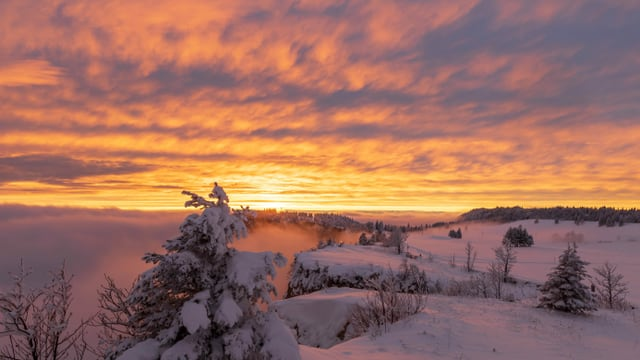 Blick über den verschneiten Grenchenberg zur untergehenden Sonne.