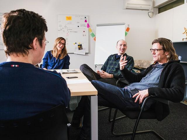Die Schreiber der Serie sitzen an einem Sitzungstisch. Sie lachen.