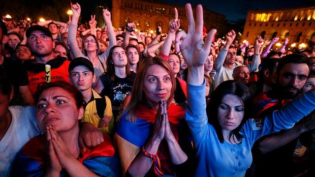 Denonstranten in der Nacht halten ihre Hände in die Höhe.