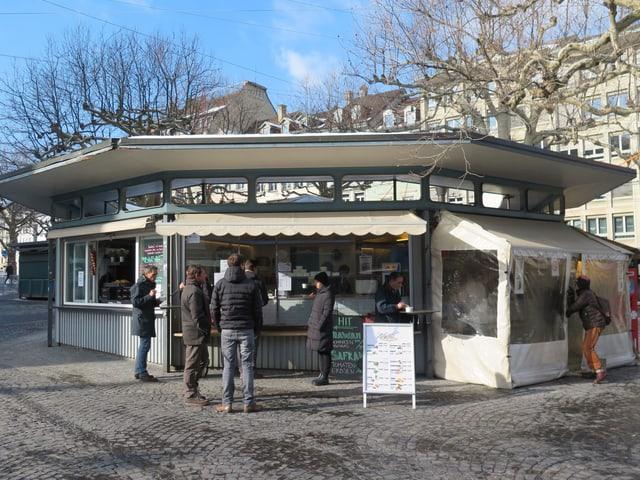Die Rondelle von aussen. Leute stehen am Kiosk an.