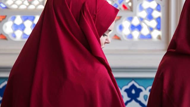 Eine Frau im Kopftuch schaut zur Seite.
