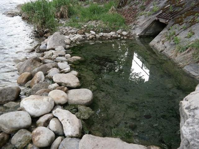 Wasser fliesst in einen Fluss zwischen Steinen.