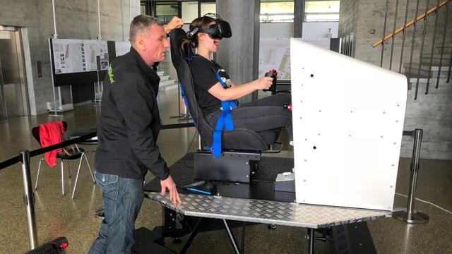 Martina sitzt mit VR Brille auf einem Flugsimulator, während Fluglehrer Christoph alles überwacht.