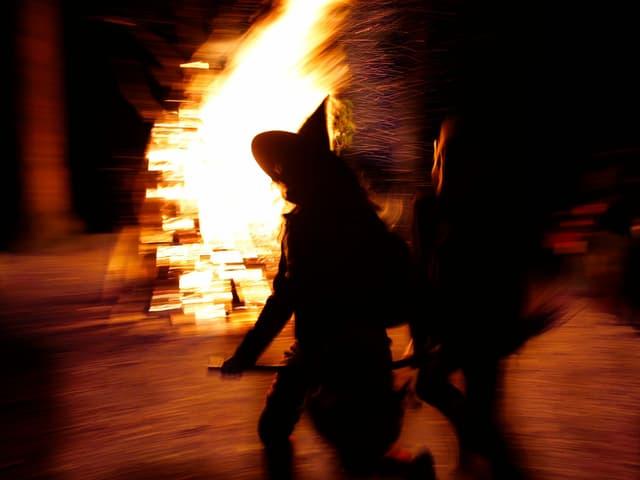 Als Hexen verkleidete Menschen rennen um ein Feuer