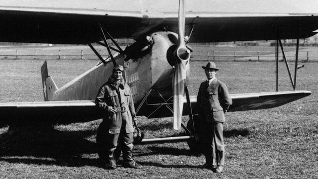 Alter Doppeldecker, davor Pilot und mann mit Hut.