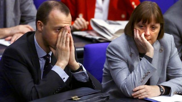 Merz und Merkel sitzen im Jahr 2000 im Reichstag nebeneinander.
