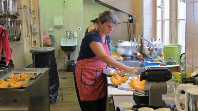 Frau Schorno bereitet in der Küche Melonenschnitze vor