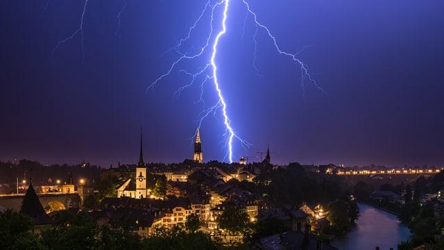 Ein Blitz schlägt direkt hinter der Stadt.