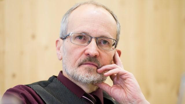 Portrait eines Mannes mit Brille und kurzem, leicht grauem Bart.