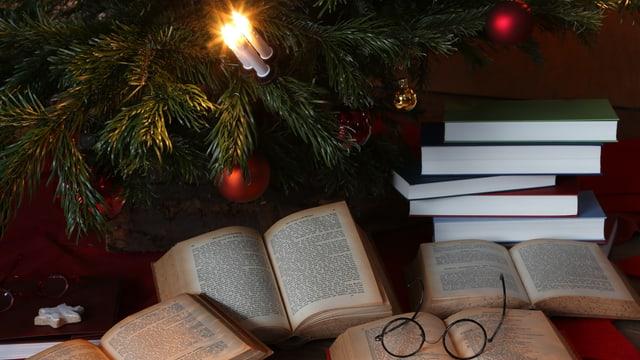 Bücher und eine Lesebrille unter dem Weihnachtsbaum.