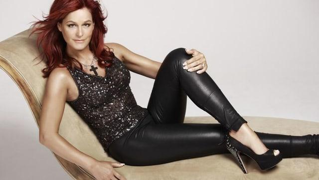 Andrea Berg räkelt sich im engen schwarzen Kleid auf einem Loungesessel.