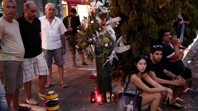 Menschen sitzen um eine Ansammlung von Blumensträussen und Kerzen, die eine Unfallstelle markieren