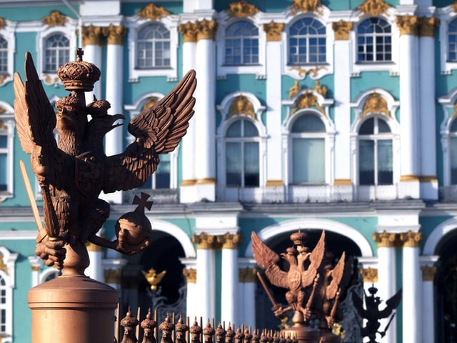 Eine Nahaufnahme des Winterpalasts: eine Adlerskulptur auf einem Zaun, im Hintergrund das türkis-weiss-goldene Gebäude.